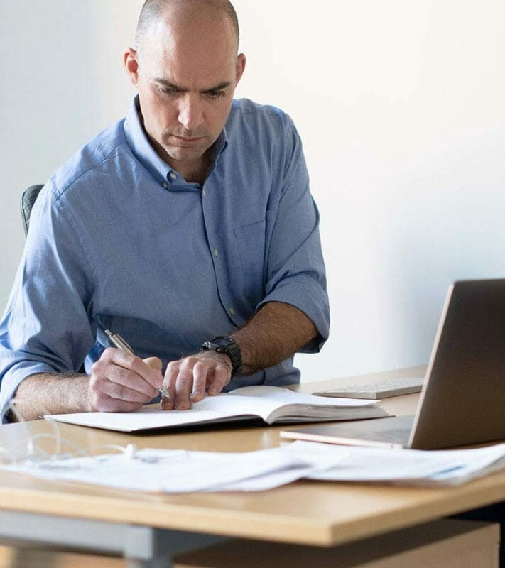 Man working at desk, writing in notepad with laptop and various papers before him
